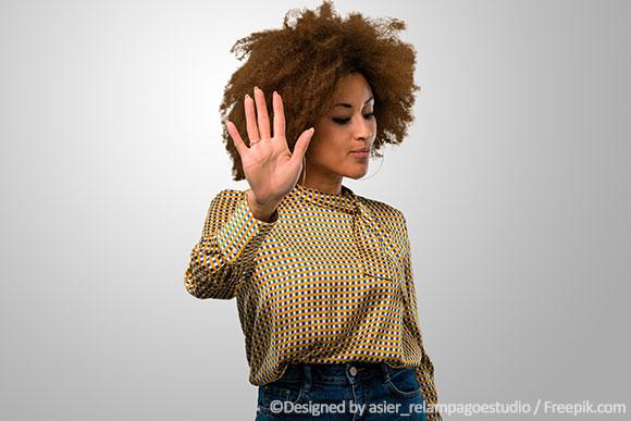 Frau mit Hormonunverträglichkeit zeigt abweisende Hand.